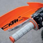 Ročica se je pri novem motociklu vrtela v prazno. Rešitev: tanka žica. EXC je serijsko opremljen z odprtimi plastičnimi ščitniki ročic.