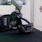 Delovanje robota za sestavljanje zračnih mehov oziroma združevanje mehov z volanskimi obroči. Sistem se v trenutku, ko zazna bližino človeške roke, zaustavi. (foto: Audi)